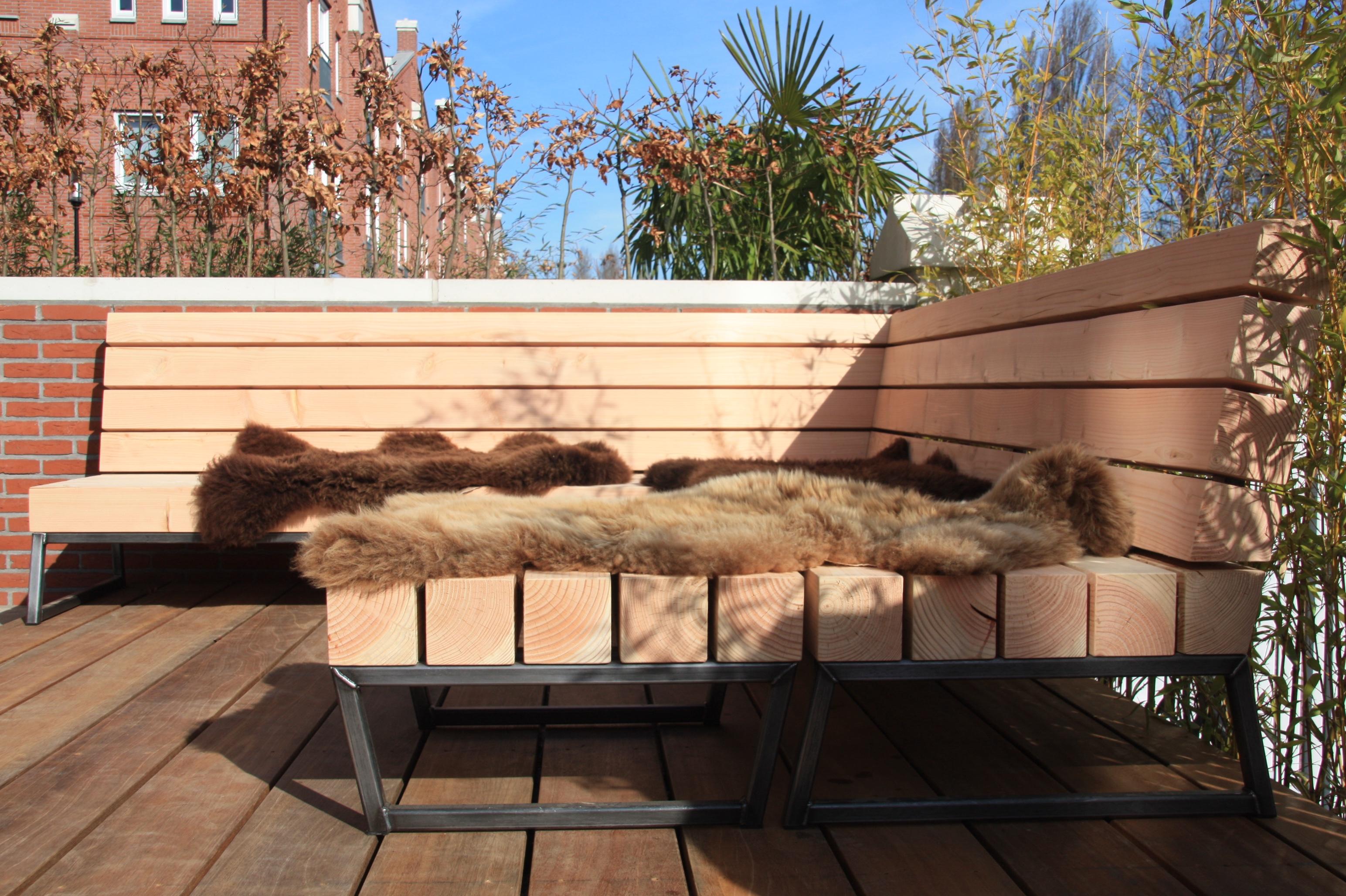 Robuuste tuin loungebank van hout en staal met gave kussens van degelijke kwaliteit en bijpassende hocker. Stoere loungeset tuin van hout. Unieke design loungebank tuin. Tuinbank douglas en staal.